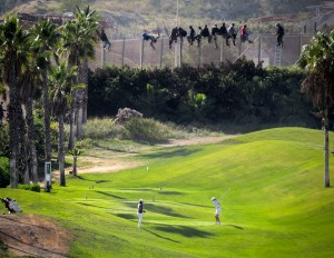 José Palazon/Reuters African asylum seekers stuck on a razor wire fence, behind white-clad golfers teeing off on a golf course.